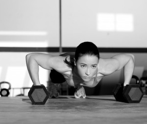 Gym woman push-up strength pushup exercise with dumbbell in a crossfit workout